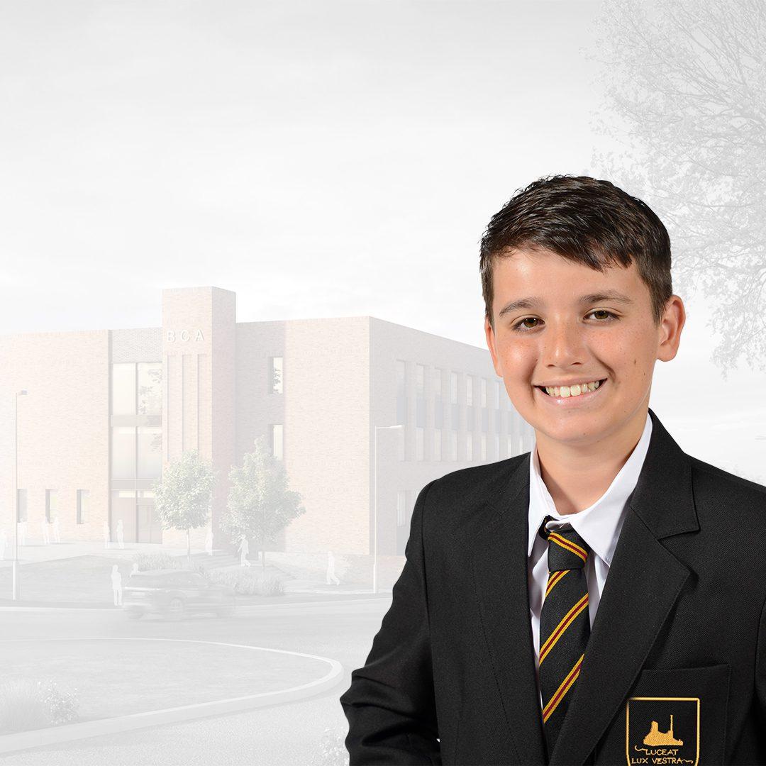 Smiling boy in Brian Clarke school uniform in front of school building